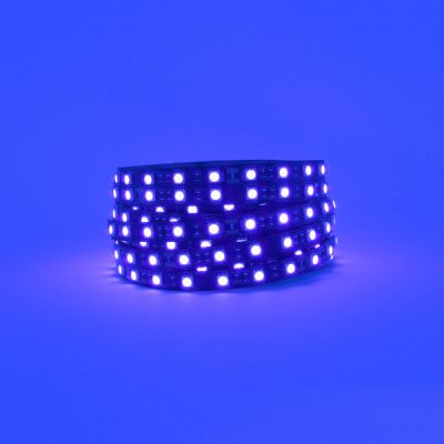 Black PCB UV LED strip lit and coiled up on purple background